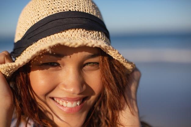 Schöne frau mit dem hut, der kamera auf strand im sonnenschein betrachtet
