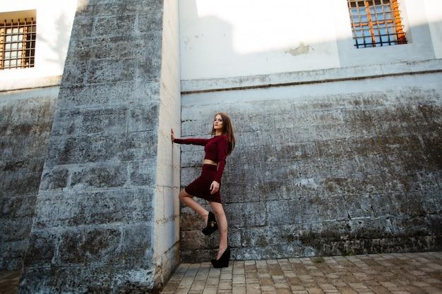 Schöne frau mit dem lockigen haar, das ein mode rotes kleid trägt, das gegen die wand steht