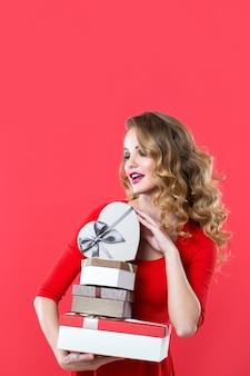 Schöne frau mit dem lockigen haar, das viele kisten über rotem hintergrund hält.