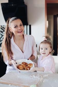 Schöne frau mit dem reizenden kind, das schüssel mit keksen hält