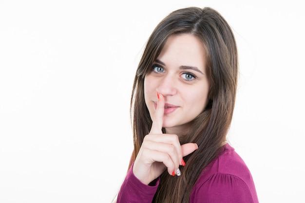 Schöne frau mit den bloßen schultern, die eine zum schweigen bringende geste bilden