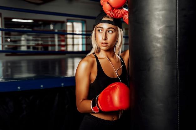 Schöne frau mit den roten boxhandschuhen. attraktives weibliches boxertraining.