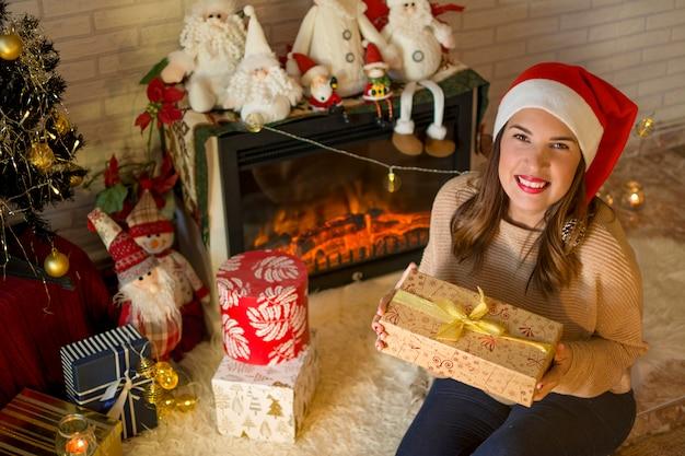 Schöne frau mit den roten lippen und weihnachtsmann-hut, ihre weihnachtsgeschenke öffnend