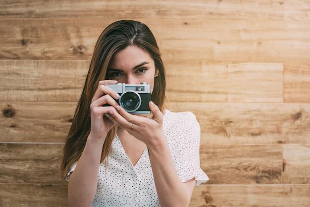 Schöne frau mit der alten kamera der weinlese, die foto macht