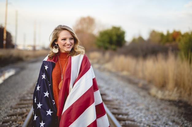 Schöne frau mit der amerikanischen flagge um ihre schultern, die auf der eisenbahn gehen