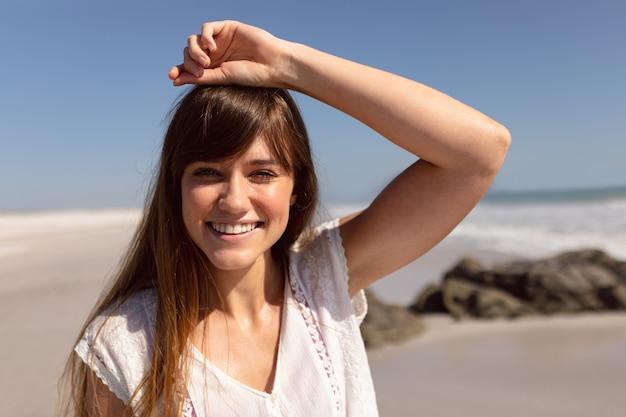 Schöne frau mit der hand auf dem kopf, der kamera auf strand im sonnenschein betrachtet