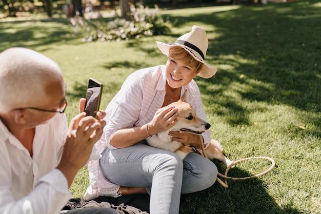 Schöne frau mit der kühlen blonden frisur im hut und im gestreiften modernen hemd, das mit hund aufwirft und auf gras mit mann mit telefon im freien sitzt.
