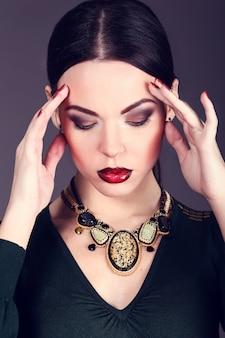 Schöne frau mit dunklem haar und abend make-up. schmuck und schönheit.