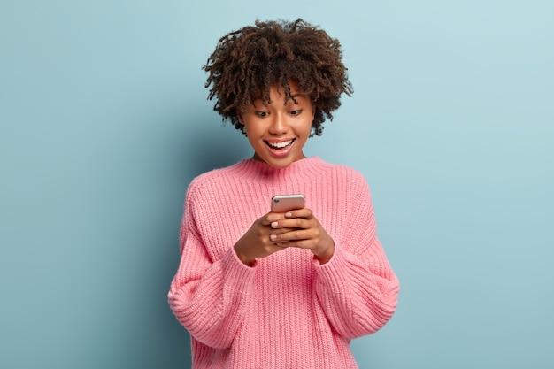 Schöne frau mit einem afro, der in einem rosa pullover aufwirft