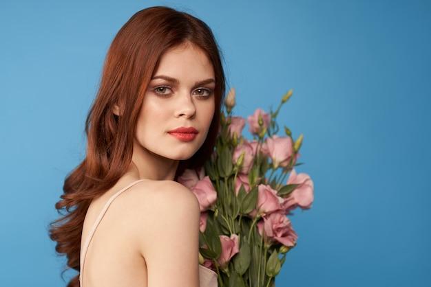 Schöne frau mit einem blumenstrauß von rosa blumen auf einem blauen raumfrühlingsmodellporträt