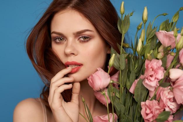 Schöne frau mit einem blumenstrauß von rosa blumen