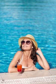 Schöne frau mit einem cocktail, das in einem pool sitzt