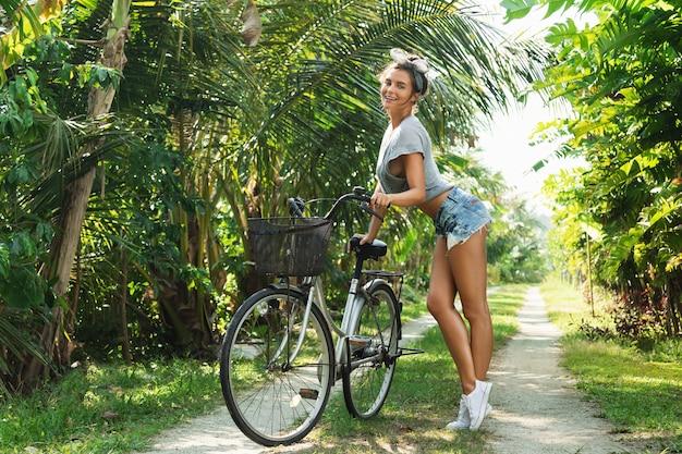Schöne frau mit einem fahrrad im tropischen garten