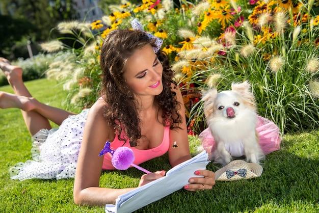 Schöne frau mit einem kleinen hund chihuahua im park