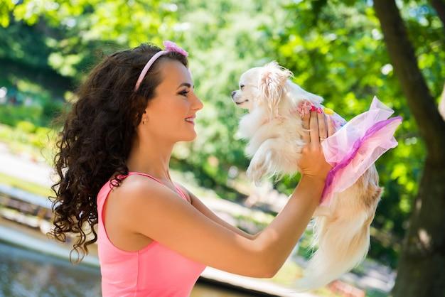 Schöne frau mit einem kleinen niedlichen hund chihuahua im park