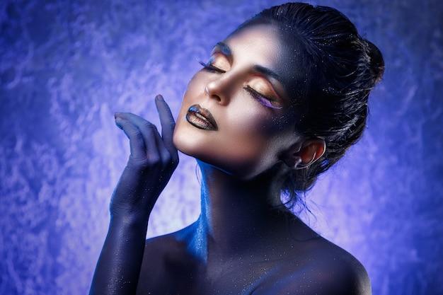 Schöne frau mit einem kreativen make-up und einer körperkunst