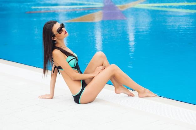 Schöne frau mit einem perfekten körper in einem badeanzug am pool