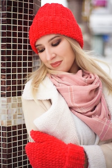 Schöne frau mit einem roten hut im winter