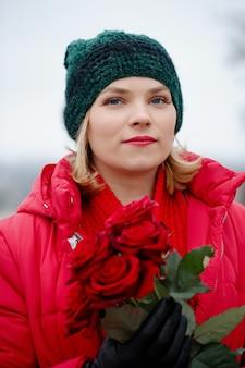 Schöne frau mit einem strauß roter rosen in ihren händen