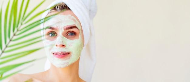 Schöne frau mit einer grünen gesichtsschönheitsmaske und einem handtuch auf ihrem kopf auf einer spa-prozedur. verschwommenes palmblatt.