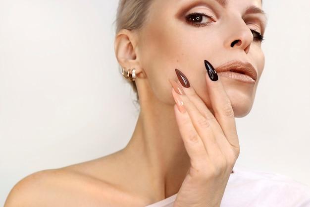 Schöne frau mit einer langen maniküre, die mit natürlichen schattierungen des nagellacks bedeckt wird
