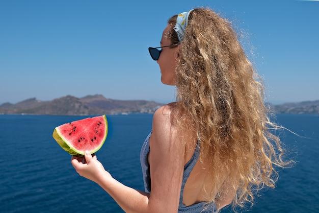 Schöne frau mit einer scheibe wassermelone, die badeanzug trägt, der rote reife wassermelonenscheibe mit meerblickfeiertags-sommer isst.