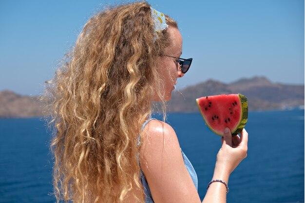 Schöne frau mit einer scheibe wassermelone im badeanzug