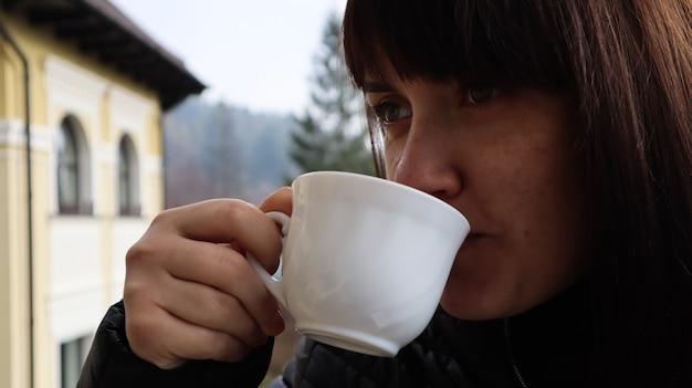 Schöne frau mit einer tasse kaffee und tee mit herrlichem blick auf die berglandschaft vom hotelbalkon. ein junges glückliches mädchen frühstückt auf dem balkon ihres hotelzimmers.