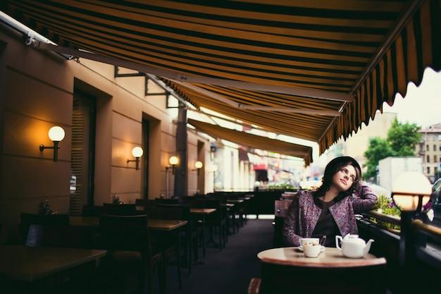 Schöne frau mit einer tasse tee, die in einem café sitzt.