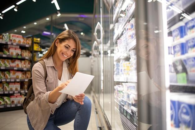 Schöne frau mit einkaufsliste, die lebensmittel im supermarkt kauft