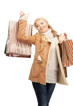 Schöne frau mit einkaufstüten über weiß