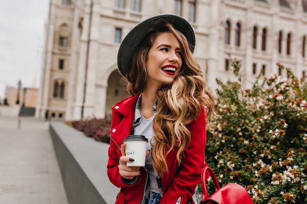 Schöne frau mit eleganter gewellter frisur, die weg schaut, während kaffee auf der straße trinkt