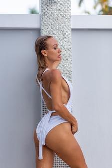 Schöne frau mit fitem körper in guter form, die entspannende dusche draußen in der villa nimmt tropenferienurlaub wasser fließt durch den körper des mädchens wasserspritzen