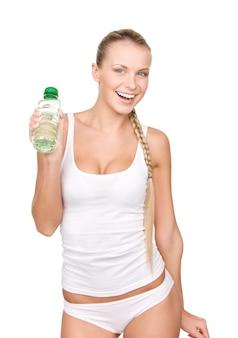 Schöne frau mit flasche wasser über weißer wand