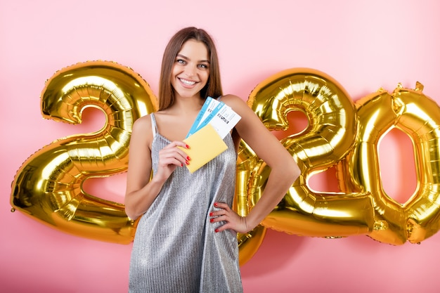 Schöne frau mit flugtickets und pass mit 2020 ballonen des neuen jahres getrennt über rosa