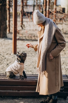 Schöne frau mit französischer bulldogge gehend in park