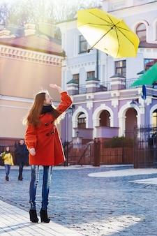 Schöne frau mit gelbem regenschirm geht durch die stadt