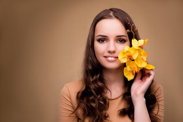 Schöne frau mit gelber orchideenblume