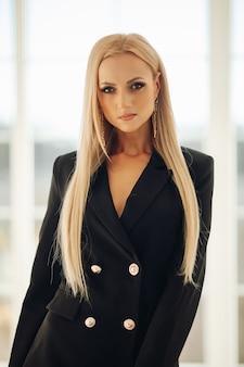 Schöne frau mit geraden blonden haaren im schwarzen stilvollen kleid, das aufwirft