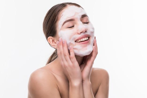 Schöne frau mit gesichtsmaske auf weißer wand. kosmetik, hautpflege.