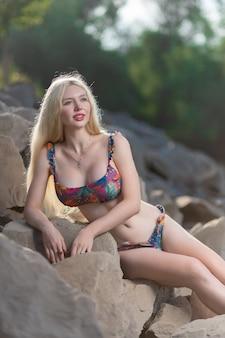 Schöne frau mit gesundem körper, die in einem colotful badeanzug ander wall trägt. das konzept des sommermode-badeanzugs und der entspannung