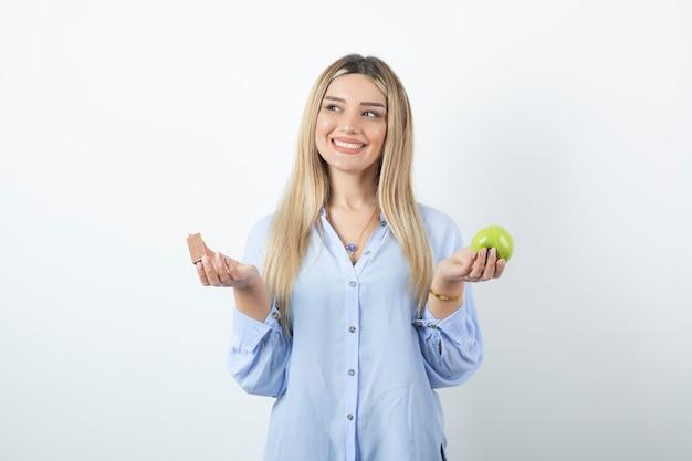 Schöne frau mit gesunden weißen zähnen, die grünen apfel halten