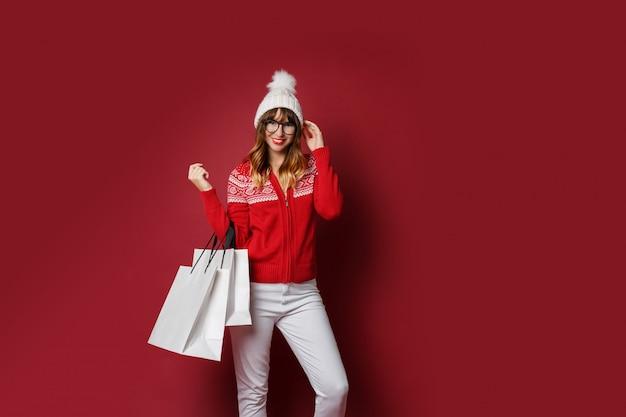 Schöne frau mit gewellten haaren, die mit weißen einkaufstüten stehen