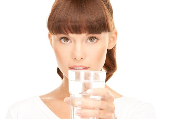 Schöne frau mit glas wasser über weiß