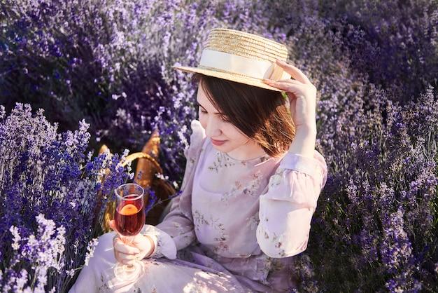 Schöne frau mit glas wein in lavendelfeldern. mädchen im strohhut entspannen auf picknick