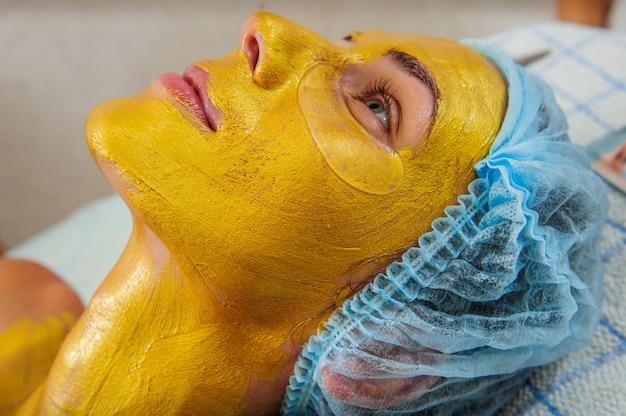Schöne frau mit goldener gesichtsmaske im schönheitssalon