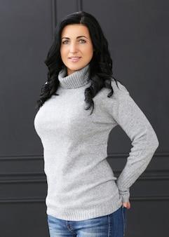 Schöne frau mit grauem pullover und jeans