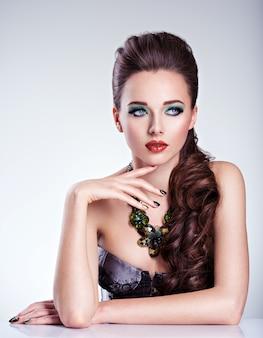 Schöne frau mit grünem make-up und kreativer farbe der nägel