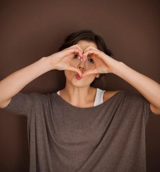 Schöne frau mit handzeichen der liebe