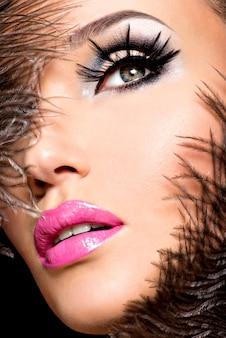 Schöne frau mit hellem professionellem make-up mit federn nahe dem gesicht.